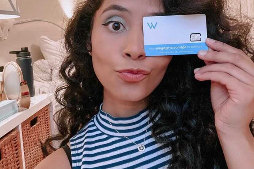 A happy new Wing user holds her SIM card for a selfie.